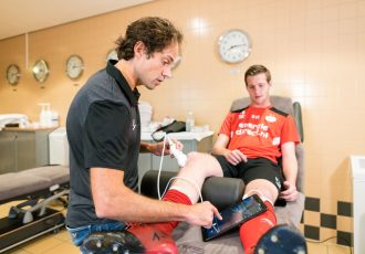 Wart van Zoest, PSV's Medical Director is using Philips' Lumify portable ultrasound to diagnose an injury of a young football player. (Photo courtesy: Philips)