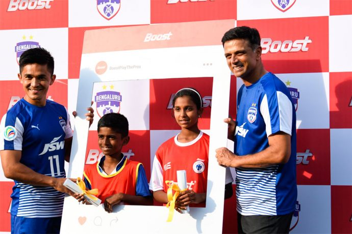 Bengaluru FC skipper Sunil Chhetri and club ambassador Rahul Dravid hand over the scholarships to Guru Kiran and Monica N. during the BFC Boost Play The Pros event held at the Bangalore Football Stadium, on Saturday. (Photo courtesy: Bengaluru FC)