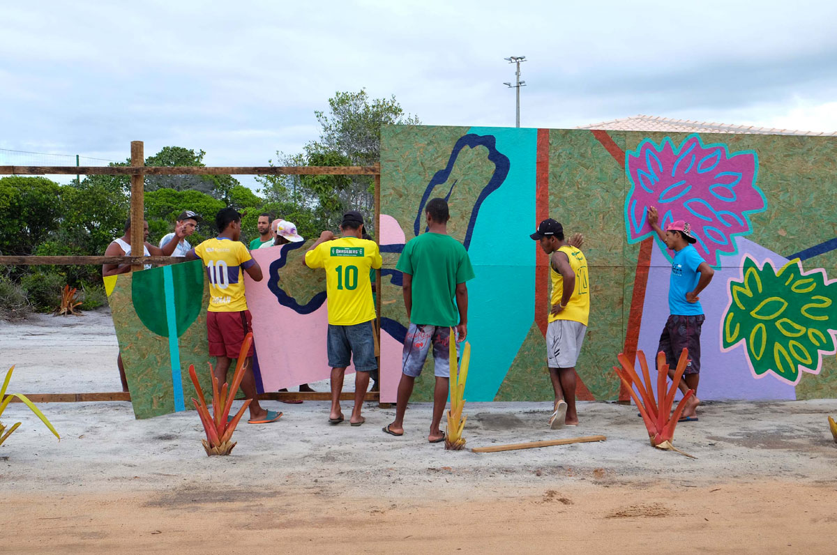 Kids of CCCultura Santo André painting the wall around Campo Bahia, the base camp of the German national football team during the 2014 FIFA World Cup. (© Theresa Ernst)