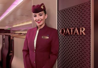 Qatar Airways cabin crew member in front of the Qsuite entrance. (Photo courtesy: Qatar Airways)