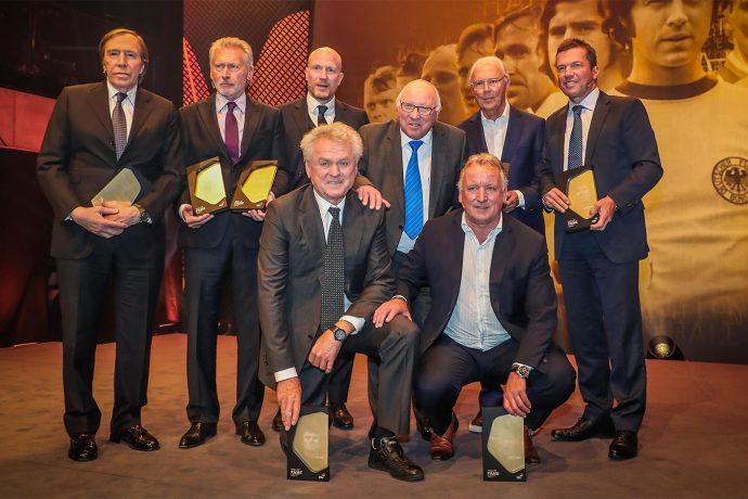Günter Netzer, Paul Breitner, Matthias Sammer, Uwe Seeler, Franz Beckenbauer, Lothar Matthäus (standing from left to right), Sepp Maier and Andreas Brehme (kneeling from left to right) at the Hall of Fame induction gala. (Photo courtesy: Deutsches Fußballmuseum)