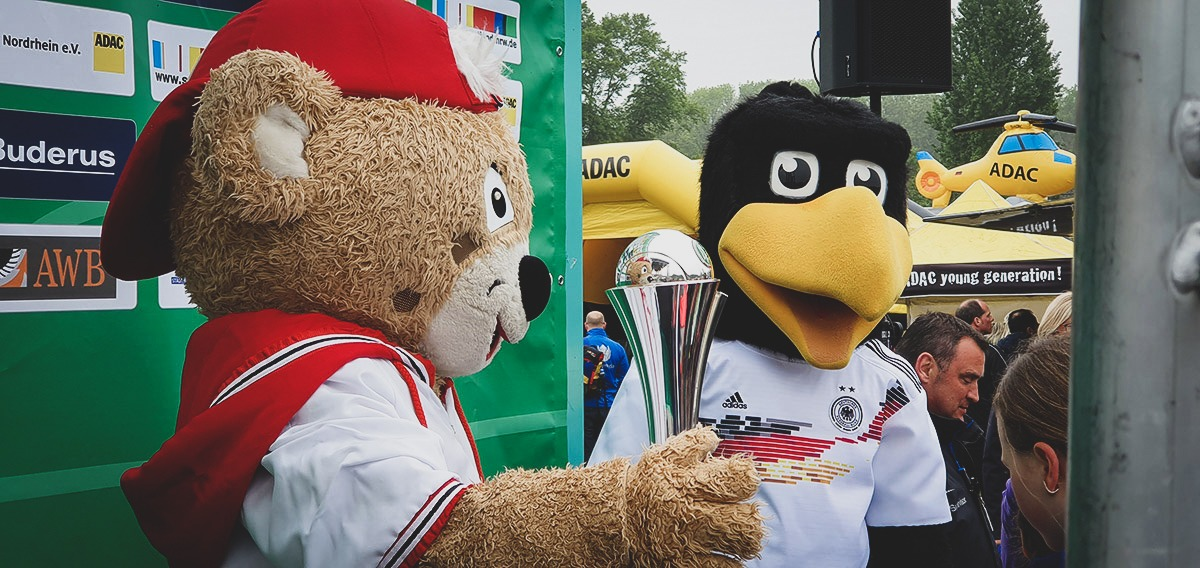 Trops, Mascot of Sports City Cologne and Paule, DFB Mascot with with the DFB-Pokal der Frauen (German Women's Cup) trophy. (© CPD Football)
