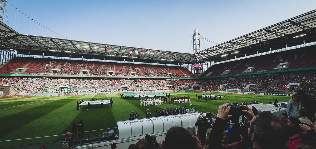 VfL Wolfsburg and SC Freiburg players lining-up for the German national anthem before kick-off. (© CPD Football)